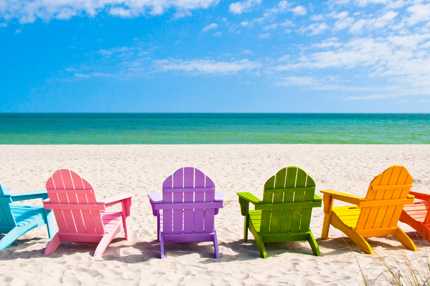 Sandy beach with colorful chairs facing ocean